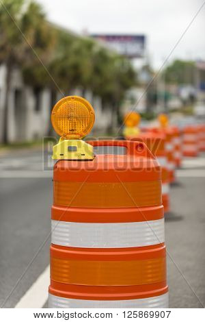 long line of orange traffic barrier barrels to detour traffic around construction zone shallow depth of field vertical