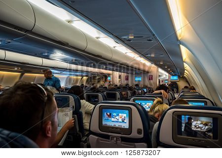 Sydney, Australia - December 10, 2015: Onboard Hawaiian Airlines Flight HA452, bound from Sydney to Honolulu. A flight attendant walks around the cabin before safety preparation procedure. Such procedure is common to all flights prior to take-off.