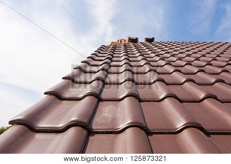 The new roof of red tiles against the blue sky.