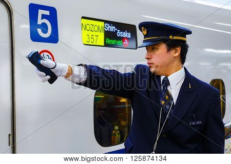 KYOTO JAPAN - NOVEMBER 23 2015: Unidentified Japanese train conductor on his duty on a Shinkansen platform at Kyoto Station