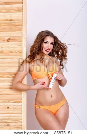 Slender attractive girl in a swimsuit. Girl holding a sign August. Shopping. Preparation for the beach season. poster