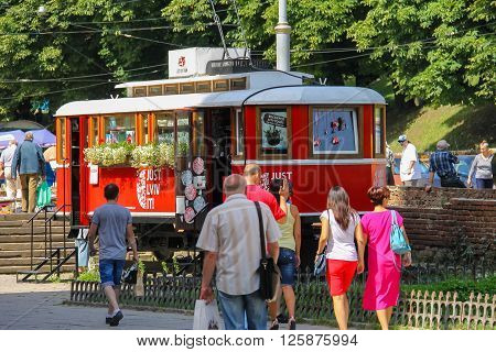 Lviv Ukraine - July 5 2014: People walking near decorative red tram (tour agency) in historic city center
