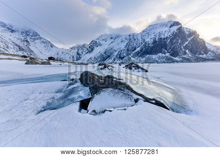 Rocks breaking through the ice at Eggum Lofoten Islands Arctic Norway Scandinavia Europe on a cloudy winter day. poster