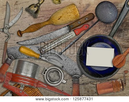 vintage utensils set for cooking over wooden table, blank business card for your text