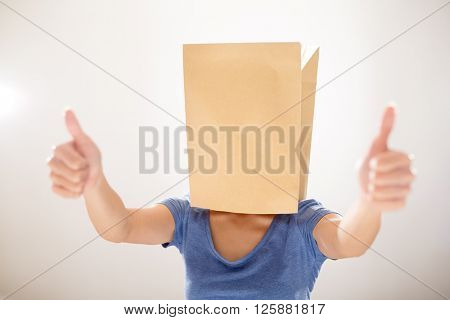 Woman with paper bag cover her head and showing thumb up
