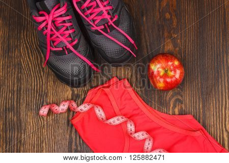 Apple sneakers and t-shirt on the wooden background