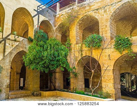 JERUSALEM ISRAEL - FEBRUARY 16 2016: The stone courtyard of Lutheran Kirche of the Redeemer with the arched galleries and tiny garden on February 16 in Jerusalem.