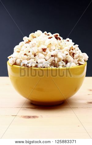 A bowl of popcorn on wood background