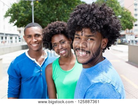 African american guy with two friends laughing at camera in the city