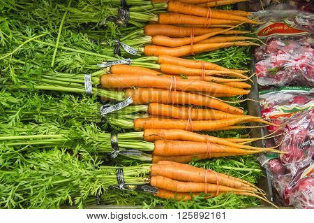 Bunch Of Fresh Carrots With Green Leaves From Market Shelves Rea