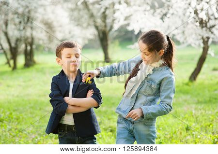 girl decorates jacket boy with flowers and   boy closed his eyes haughtily