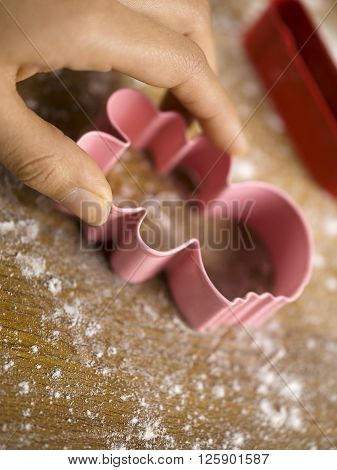 Hand Holding Cookie Cutter On Wooden Worktop
