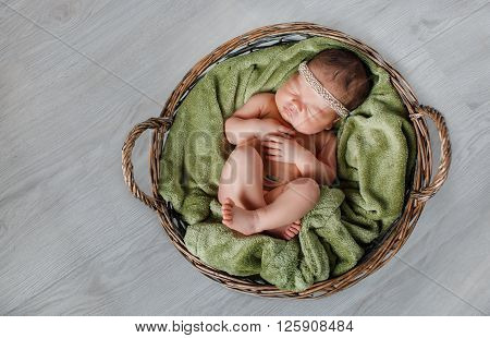 Peaceful sleep of a newborn baby on a gray background ,handsome kid who wore a wreath on his head, sleeping sweetly tucked arms and legs on a green blanket in brown wicker basket
