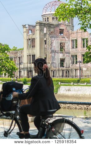 Hiroshima, Japan - July 10, 2014: A Japanese girl is cycling past the Atomic Bomb Dome (aka Hiroshima Peace Memorial) that was destroyed by the Atomic Bombing of Hiroshima (