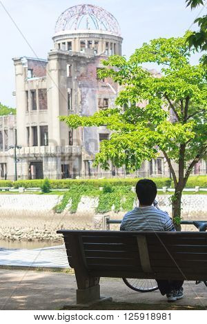 Hiroshima, Japan - July 10, 2014: A Japanese man sits on a bench next to the Aioi River across the Atomic Bomb Dome (Hiroshima Peace Memorial) that was destroyed by the Atomic Bombing of Hiroshima (