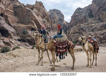 PETRA, JORDAN - NOVEMBER 22, 2007: Unidentified local Bedouin guided on camels near Royal tombs. The city of Petra was lost for over 1000 years. Now one of the Seven Wonders of the Word