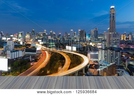 Opeing wooden floor, View of the Bangkok Skyscraper with highway during twilight