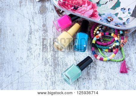 nail polish and bracelets for summer on a white wooden background