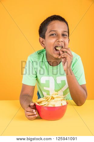 cute little indian boy eating chips or potato wafers, asian boy eating potato chips,  small boy eating chips in red bowl, over yellow background