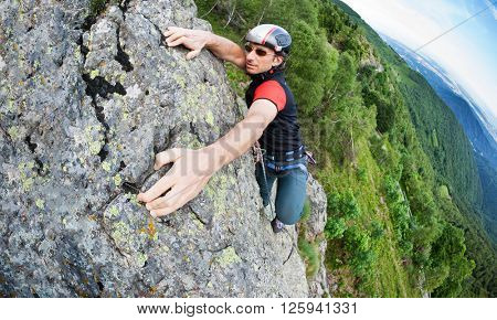 A free-climber reaches the top of a rocky wall. Concept: courage, success, perseverance, effort, self-realization. Italian Alps, Italy.