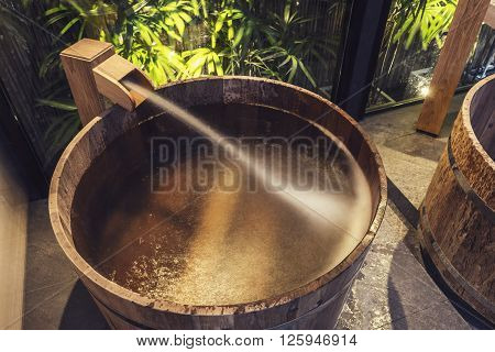 Onsen series : Water streaming into wooden bathtub