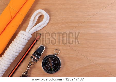Orderliness White Scout Rope, Scarf, Whistle, Pencil And Compass On Wooden Table.