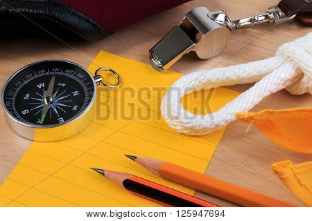 Orderliness White Scout Rope, Scarf, Whistle, Compass, Pencil And Paper Note On Wooden Table.