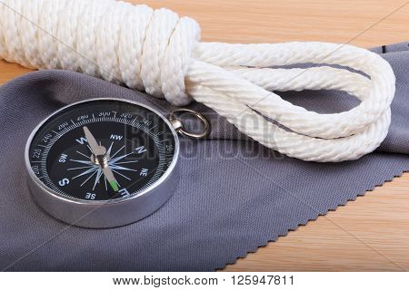 Orderliness White Scout Rope, Compass And Fabric On Wooden Table.