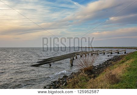 Marken is particularly colorful peninsula in the Markermeer. This picture of breakwaters was taken from an embankment on December 20, 2015.