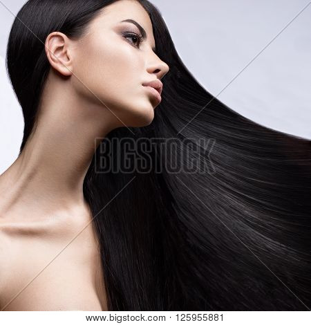Beautiful brunette girl in move with a perfectly smooth hair and classic make-up. Beauty face. Picture taken in the studio on a white background.