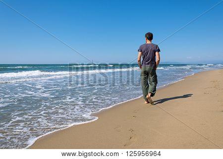 footprints of a man walking on the beach barefoot
