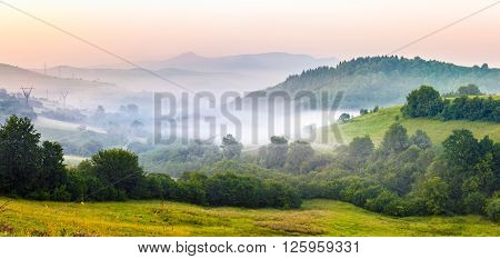 idyllic summer landscape with cold morning fog on hillside in mountainous rural area before sunrise