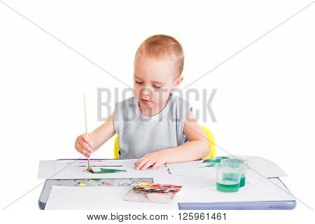 Little boy makes his first drawings in watercolor. Isolated on a white background.