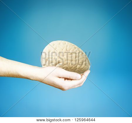 Male hand holding brain on blue background