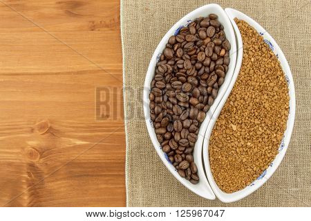 Natural coffee beans versus instant. Soluble and coffee beans on wooden background. Preparing fresh coffee. Sales of roasted coffee. Advertising for the sale of coffee.
