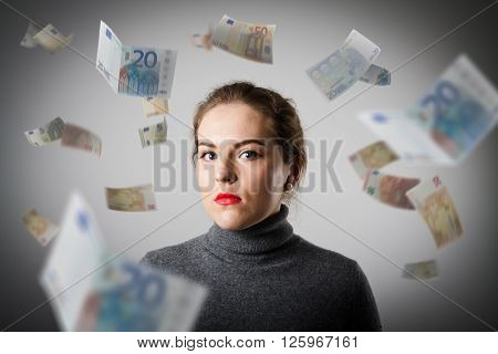Girl in grey and falling Euro banknotes. Currency and lottery concept.