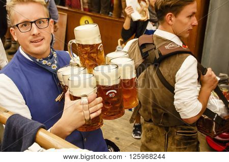 MUNICH, GERMANY - OCTOBER 02, 2015: Inside the Braeurosl beer tent with a waiter serving beer