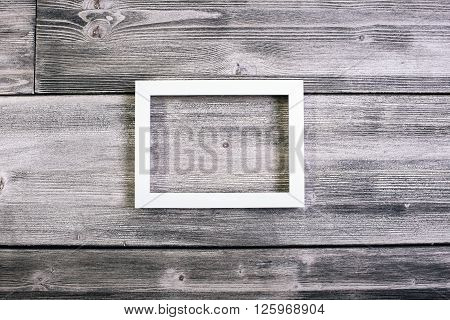 Rectangular see-through frame hanging on wooden wall. Mock up