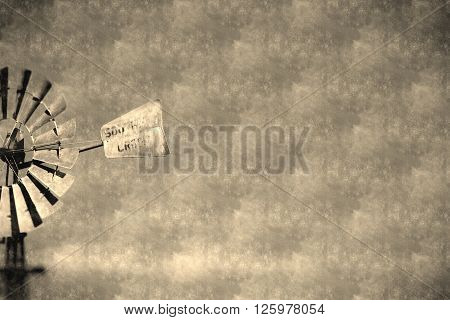 Background abstracts of Vintage Australian Windmill on rural farming property pumping live stock bore from underground water table in salty, saline outback environment with plenty of history