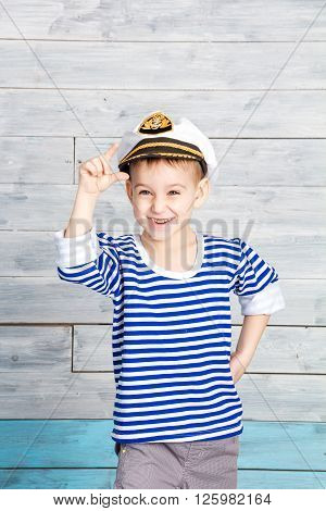 little boy holding on to his cap and laughs looking at camera