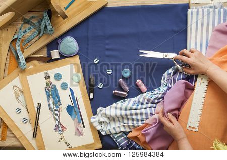 Desk designer fashion. Fashion designer starts cutting fabric to create fashionable clothes on the sketches.
