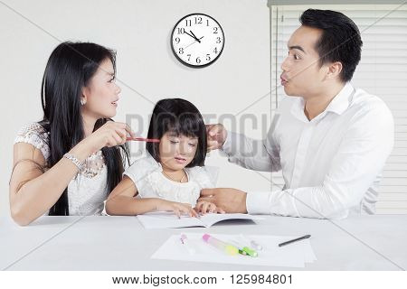 Image of two young parents quarreling and blaming each other in front of their daughter at home