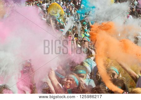 HAMPTON, GA - APRIL 2016:  A huge crowd of runners who completed the Color Run toss packets of colored corn starch into the air creating an organic explosion of colors over the group in Hampton GA on April 2 2016 .
