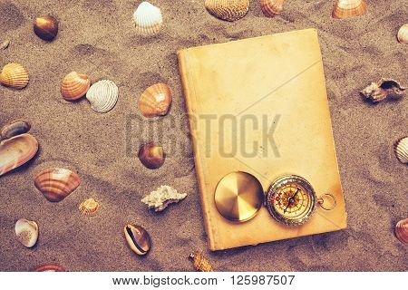 Vintage book and compass on sandy beach, top view
