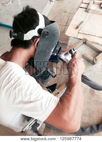 A worker welding construction by argon welding