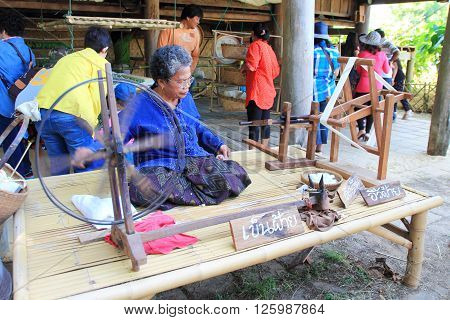 NAKHONRATCHASIMA THAILAND- DECEMBER 14 : unidentified woman spinning silk in Jim Thompson Farm on DECEMBER 14 2014 in NAKHONRATCHASIMA THAILAND. The House of the world renowned Jim Thompson Thai Silk.