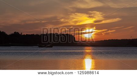 Nordic night in the archipelago of the Baltic Sea. Small boat cruises by in the night. Sunset, nightfall.