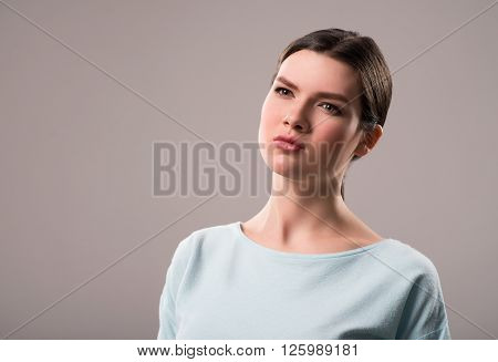 Serious intention. Pleasant asserted  thoughtful girl  looking aside and expressing  confidence while standing isolated on grey background