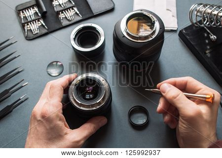 Photo camera lens repair set. Technician engineer check optics alignment and maintenance support of broken photographic 50 1.4 photo camera lens part. Pov to workplace and engineer's hands.