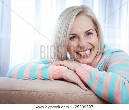 Active beautiful middle-aged woman smiling friendly and looking into the camera at home in living room. Woman's face close up.